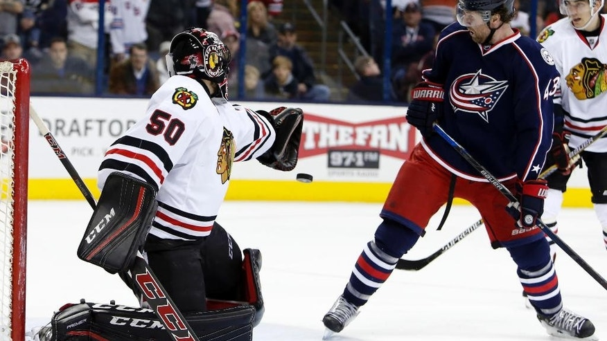 Columbus Blue Jackets' Scott Hartnell, right, deflects the puck into the goal against Chicago Blackhawks' Corey Crawford during the overtime period of an NHL hockey game Saturday, April 9, 2016, in Columbus, Ohio. The Blue Jackets beat the Blackhawks 5-4 in overtime. (AP Photo/Jay LaPrete)