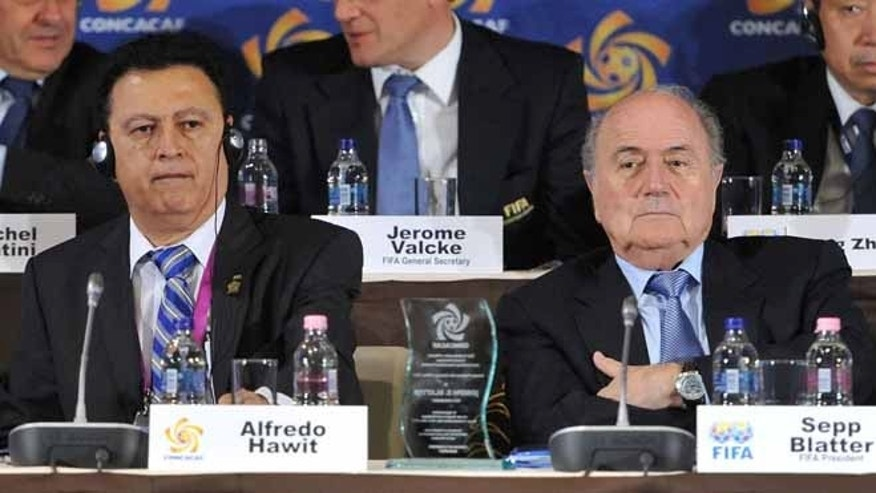 In this May 23, 2012 file photo, Alfredo Hawit of Honduras, left, interim head of CONCACAF, and FIFA President Joseph Blatter sit next to each other  at the CONCACAF presidential election in Budapest, Hungary. Hawit has pleaded guilty, Monday, April 11, 2016,  to four conspiracy counts in the sweeping FIFA bribery scandal over lucrative broadcast rights. Prosecutors in New York said Alfredo Hawit accepted bribes totaling hundreds of thousands of dollars linked to the sale of marketing rights to tournaments in Latin America. (Szilard Koszticsak/MTI via AP, File)