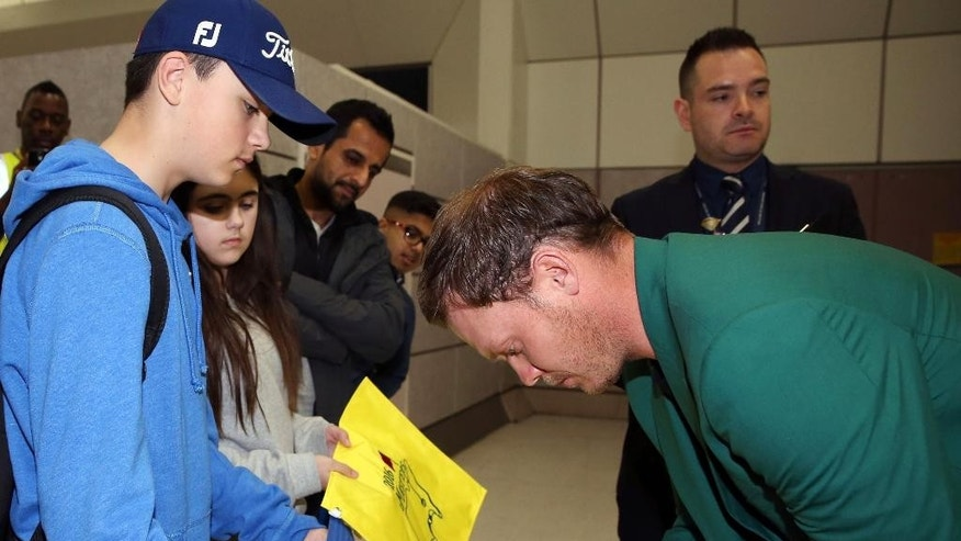Britain's Danny Willett signs an autographs as he arrives at Manchester Airport, England, Tuesday April 12, 2016, after his victory at the Masters on Sunday. Willett arrived back in Britain having become the first European to win the Masters since 1999 and only the second English player to receive the green jacket. (Martin Rickett/PA via AP) UNITED KINGDOM OUT