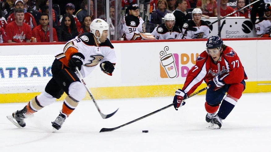Anaheim Ducks defenseman Clayton Stoner (3) knocks the puck past Washington Capitals right wing T.J. Oshie (77) in the first period of an NHL hockey game, Sunday, April 10, 2016, in Washington. (AP Photo/Alex Brandon)