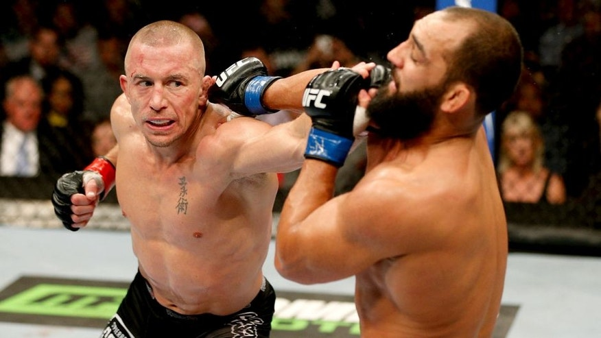 LAS VEGAS, NV - NOVEMBER 16: (L-R) Georges St-Pierre punches Johny Hendricks in their UFC welterweight championship bout during the UFC 167 event inside the MGM Grand Garden Arena on November 16, 2013 in Las Vegas, Nevada. (Photo by Josh Hedges/Zuffa LLC/Zuffa LLC via Getty Images)