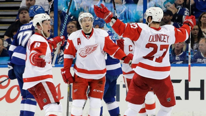 Detroit Red Wings left wing Justin Abdelkader (8) celebrates his goal against the Tampa Bay Lightning with teammates center Pavel Datsyuk (13), of Russia, and defenseman Kyle Quincey (27) during the second period of Game 1 in a first-round NHL hockey Stanley Cup playoff series Wednesday, April 13, 2016, in Tampa, Fla. (AP Photo/Chris O'Meara)