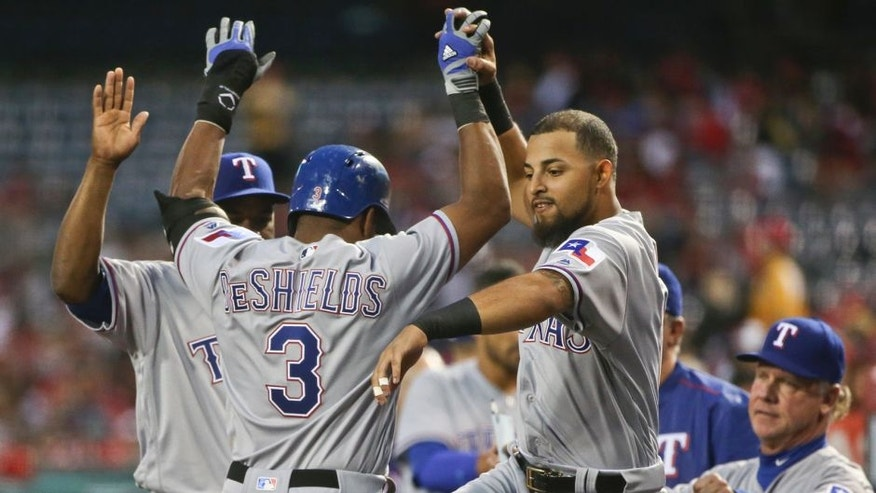 Texas Rangers' Rougned Odor greets Delino DeShields after DeShields scored in their three-run first inning against the Los Angeles Angels in a baseball game Friday, April 8, 2016, in Anaheim, Calif. (AP Photo/Lenny Ignelzi)