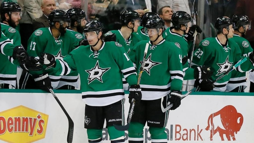 FILE - In this Jan. 25, 2016, file photo, Dallas Stars' Patrick Sharp (10) and Jason Spezza (90) are congratulated by the bench after Spezza scored a goal against the Calgary Flames in the second period of an NHL hockey game in Dallas. Known as the North Stars before moving south to Dallas in 1993, the Stars are the top seed in the Western Conference playoffs. They open their first-round best-of-seven series at home Thursday night against the Wild, the team that later replaced them in Minnesota.  (AP Photo/Tony Gutierrez, File)