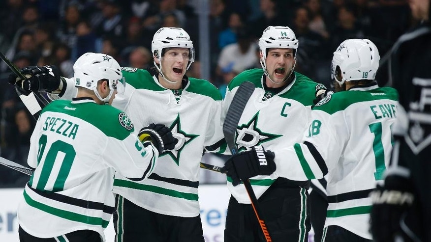 FILE - In this April 2, 2016, file photo, Dallas Stars left wing Jamie Benn, second from right, celebrates his power play goal with teammates, from left to right, Jason Spezza, John Klingberg and Patrick Eaves during the first period of an NHL hockey game against the Los Angeles Kings, in Los Angeles. Benn always seems uncomfortable in the spotlight, even after general manager Jim Nill and coach Lindy Ruff made him the captain soon after they arrived in Dallas in 2013. He's growing into the role, and the Stars are the top seed in the Western Conference for the first time since Mike Modano was the face of the franchise in 2003. (AP Photo/Danny Moloshok, File)