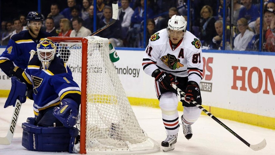 Chicago Blackhawks' Marian Hossa, of Slovakia, brings the puck behind the net as St. Louis Blues goalie Brian Elliott, left, defends during the first period in Game 1 of an NHL hockey first-round Stanley Cup playoff series Wednesday, April 13, 2016, in St. Louis. (AP Photo/Jeff Roberson)