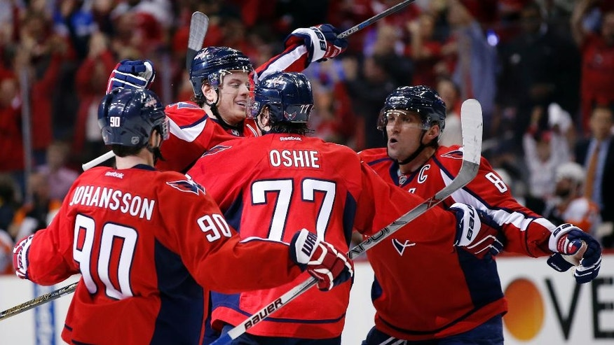 Washington Capitals center Marcus Johansson (90), from Sweden, right wing T.J. Oshie (77) and left wing Alex Ovechkin (8), from Russia, celebrate with defenseman John Carlson, second from left, after his goal against the Philadelphia Flyers during the second period of Game 1 of a first-round NHL hockey Stanley Cup playoff series Thursday, April 14, 2016, in Washington. (AP Photo/Alex Brandon)