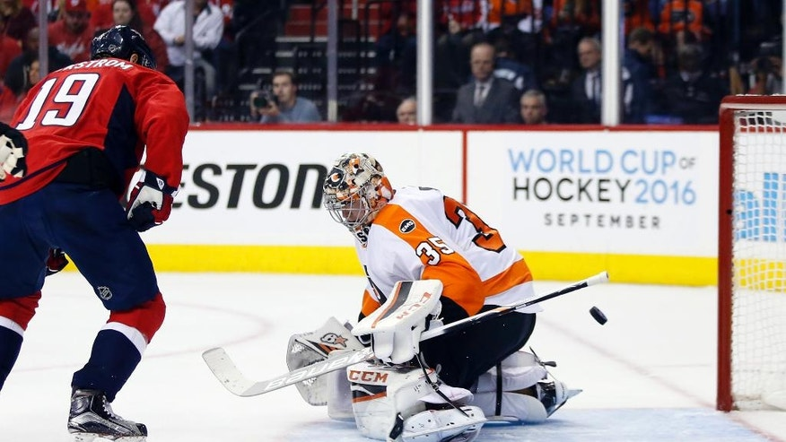 A goal by Washington Capitals defenseman John Carlson gets past Philadelphia Flyers goalie Steve Mason (35) with Washington Capitals center Nicklas Backstrom, left, from Sweden, nearby, during the second period of Game 1 of a first-round NHL hockey Stanley Cup playoff series Thursday, April 14, 2016, in Washington. (AP Photo/Alex Brandon)