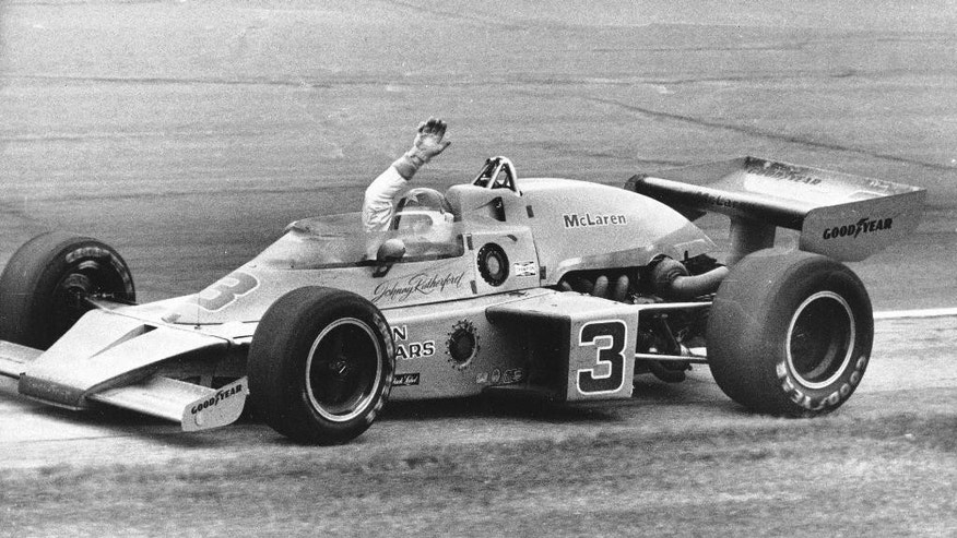 FILE - In this May 26, 1974, file photo, Johnny Rutherford waves race car after winning the 58th running of the Indianapolis 500 auto race at Indianapolis Motor Speedway in Indianapolis, Ind.  (AP Photo/File)