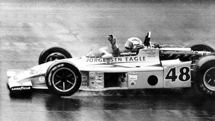 FILE - In this May 25, 1975, file photo, Bobby Unser waves as he cautiously drives his Eagle-Turbo Offy across the finish line to win the rain-shortened Indianapolis 500 auto race at Indianapolis Motor Speedway in Indianapolis, Ind.(AP Photo/File)