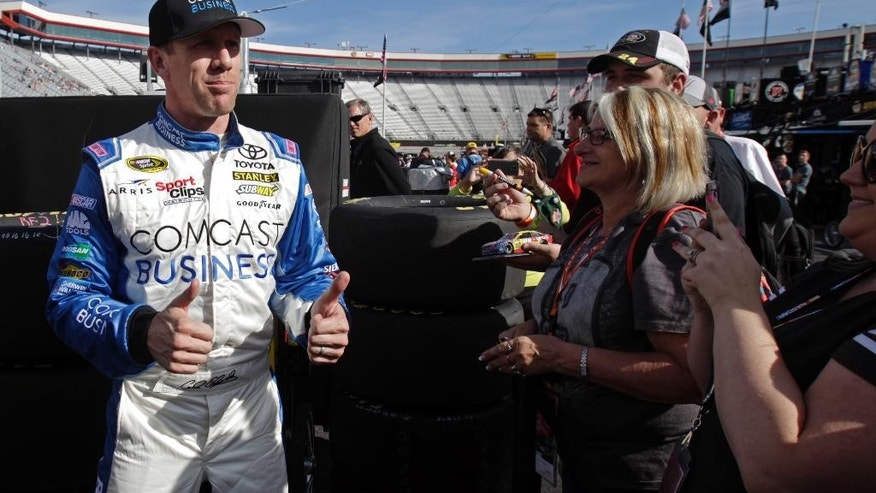 Sprint Cup Series driver Carl Edwards (19) gives two thumbs-up to fans after winning the pole for a NASCAR auto race, Friday, April 15, 2016, in Bristol, Tenn. (AP Photo/Wade Payne)