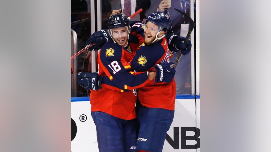 Florida Panthers right wing Reilly Smith (18) and left wing Jonathan Huberdeau (11) celebrate after Smith scored during the first period of Game 2 in a first-round NHL hockey Stanley Cup playoff series against the New York Islanders, Friday, April 15, 2016, in Sunrise, Fla. (AP Photo/Wilfredo Lee)