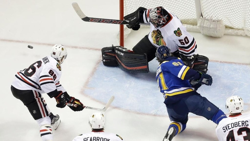 Chicago Blackhawks goalie Corey Crawford, top, deflects a shot from St. Louis Blues' Vladimir Tarasenko, of Russia, as Blackhawks' Teuvo Teravainen (86), of Finland, and Brent Seabrook (7) watch during the first period in Game 2 of an NHL hockey first-round Stanley Cup playoff series Friday, April 15, 2016, in St. Louis. (AP Photo/Jeff Roberson)
