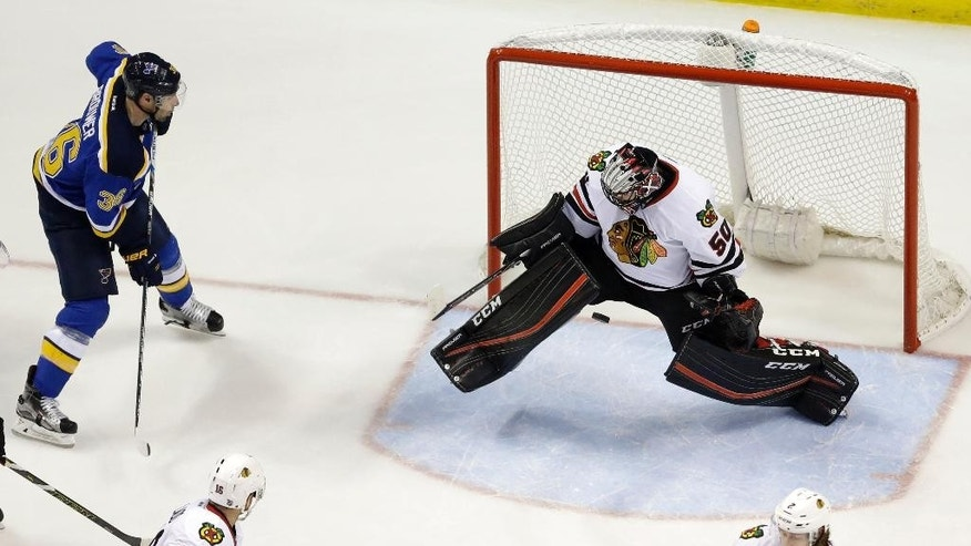Chicago Blackhawks goalie Corey Crawford deflects a puck as St. Louis Blues' Troy Brouwer, left, watches during the first period in Game 2 of an NHL hockey first-round Stanley Cup playoff series Friday, April 15, 2016, in St. Louis. (AP Photo/Jeff Roberson)