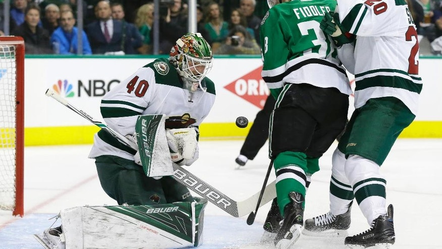 Minnesota Wild goalie Devan Dubnyk (40) and defenseman Ryan Suter (20) defend the goal against Dallas Stars center Vernon Fiddler (38) during the first period of Game 1 in a first-round NHL hockey Stanley Cup playoff series Thursday, April 14, 2016, in Dallas. (AP Photo/LM Otero)