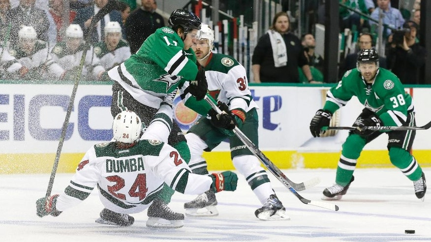 Minnesota Wild defenseman Matt Dumba (24) is knocked off his feet by Dallas Stars center Mattias Janmark (13) as Wild defenseman Nate Prosser (39) and Stars center Vernon Fiddler (38) watch during the first period of Game 1 in a first-round NHL hockey Stanley Cup playoff series Thursday, April 14, 2016, in Dallas. (AP Photo/LM Otero)