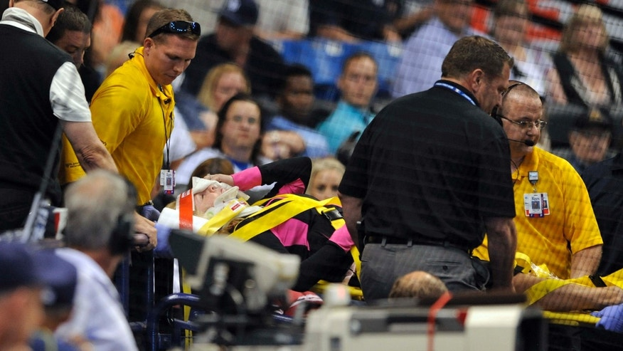 Medical personnel carry a fan from the stands by stretcher after she was hit a foul ball from Tampa Bay Rays designated hitter Steven Souza Jr. during the seventh inning of a baseball game against the Chicago White Sox, Friday, April 15, 2016, in St. Petersburg, Fla.