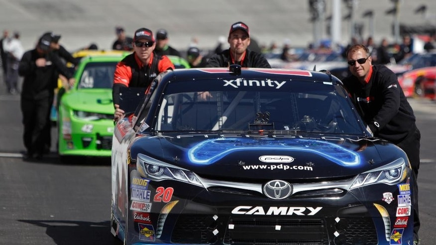 The crew of pole sitter Eric Jones moves his car the the starting grid before a NASCAR Xfinity Series auto race on Saturday, April 16, 2016 in Bristol, Tenn. (AP Photo/Wade Payne)