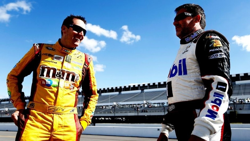 LONG POND, PA - JUNE 06: Kyle Busch, driver of the #18 M&M's Peanut Butter Toyota, left, talks with Tony Stewart, driver of the #14 Mobil 1/Bass Pro Shops Chevrolet, on the grid during qualifying for the NASCAR Sprint Cup Series Pocono 400 at Pocono Raceway on June 6, 2014 in Long Pond, Pennsylvania. (Photo by Jeff Zelevansky/Getty Images)