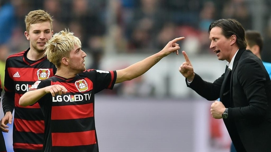 Leverkusen;s Kevin Kampl, left, celebrates after scoring the first goal beside Leverkusen head coach Roger Schmidt, right, during the German Bundesliga soccer match between Bayer Leverkusen and Eintracht Frankfurt in Leverkusen, Germany, Saturday, April 16, 2016. (AP Photo/Martin Meissner)