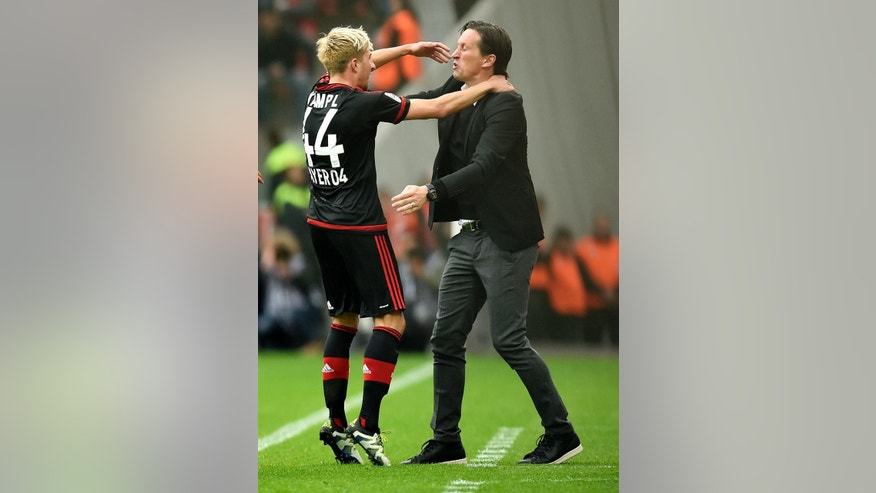 Leverkusen' s Kevin Kampl celebrates with Leverkusen head coach Roger Schmidt after scoring the opening  goal during the German Bundesliga soccer match between Bayer Leverkusen and Eintracht Frankfurt in Leverkusen, Germany, Saturday, April 16, 2016. (AP Photo/Martin Meissner)
