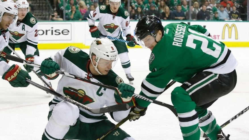 Minnesota Wild center Mikko Koivu (9) and Dallas Stars left wing Antoine Roussel (21) battle for the puck during the first period in Game 2 in the first round of the NHL Stanley Cup playoffs Saturday, April 16, 2016, in Dallas. (AP Photo/LM Otero)