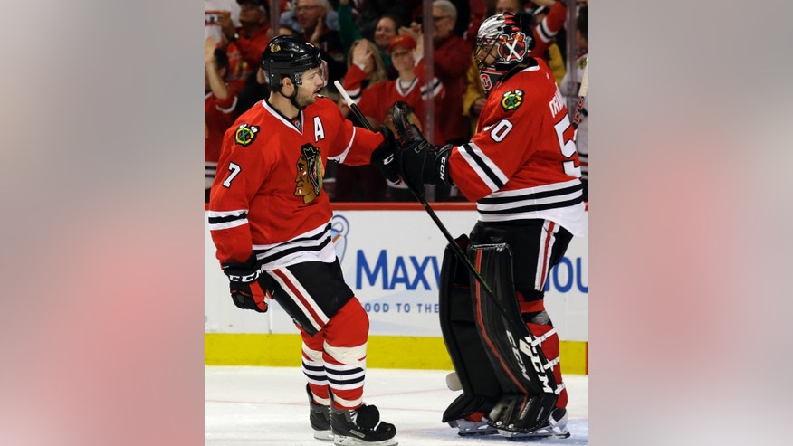 Chicago Blackhawks defenseman Brent Seabrook, left, celebrates with goalie Corey Crawford after scoring his goal during the first period in Game 3 of an NHL hockey first-round Stanley Cup playoff series against the St. Louis Blues, Sunday, April 17, 2016, in Chicago. (AP Photo/Nam Y. Huh)