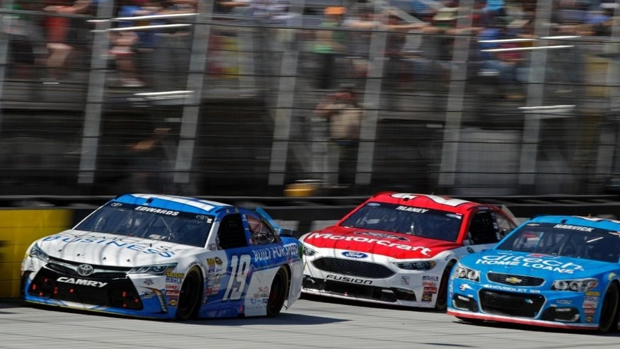 Sprint Cup Series driver Carl Edwards (19) leads Kevin Harvick (4) and Ryan Blaney in a NASCAR Sprint Cup Series auto race, Sunday, April 17, 2016, in Bristol, Tenn. (AP Photo/Wade Payne)