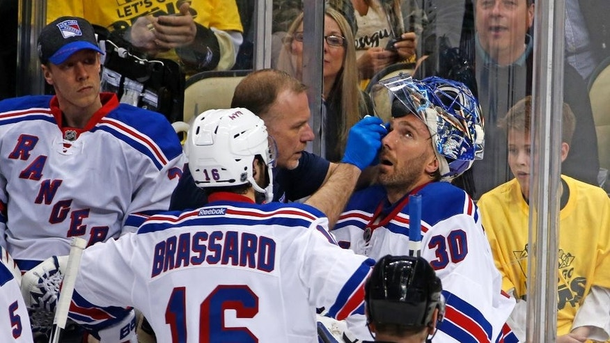 FILE - In this April 13, 2016, file photo, New York Rangers goalie Henrik Lundqvist (30) is attended to by a trainer after getting a stick to the face during the first period of a first-round NHL playoff hockey game against the Pittsburgh Penguins in Pittsburgh. Even after taking an accidental stick to the eye, Lundqvist doesn't want to see changes to masks. His fellow NHL goalies agree. (AP Photo/Gene J. Puskar, File)