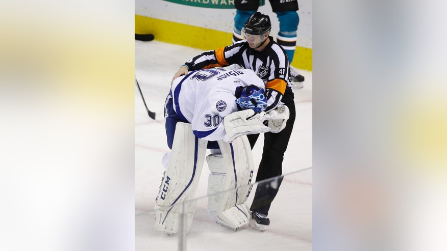FILE - In this Dec. 5, 2015, file photo, Tampa Bay Lightning goalie Ben Bishop is assisted by referee Steve Kozari after being injured during the third period of an NHL hockey game against the San Jose Sharks in San Jose, Calif. Even after taking an accidental stick to the eye, New York Rangers goaltender Henrik Lundqvist doesn't want to see changes to masks. Even though Marc-Andre Fleury of the Pittsburgh Penguins, Bishop and Philipp Grubauer of the Washington Capitals have been clipped in the face by sticks just this season, many of his colleagues around the league tend to agree, prioritizing the value of seeing the puck over the increased safety of a mask with more bars that would obscure vision. (AP Photo/Eric Risberg, File)