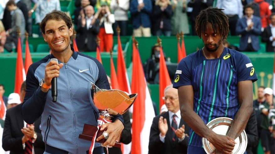 Spain's Rafael Nadal holds his cup after defeating France's Gael Monfils, right, in the final match of the Monte Carlo Tennis Masters tournament in Monaco, Sunday, April 17, 2016. (AP Photo/Lionel Cironneau)