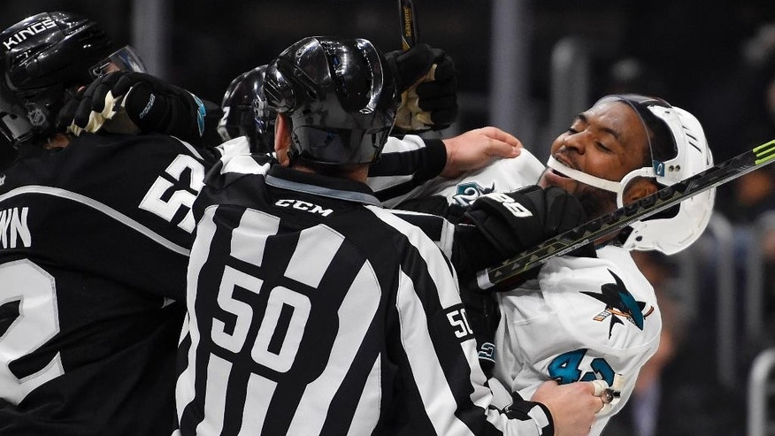 Los Angeles Kings defenseman Luke Schenn, left, and San Jose Sharks right wing Joel Ward tussle during the first period of Game 2 in an NHL hockey Stanley Cup playoffs first-round series, Saturday, April 16, 2016, in Los Angeles. (AP Photo/Mark J. Terrill)