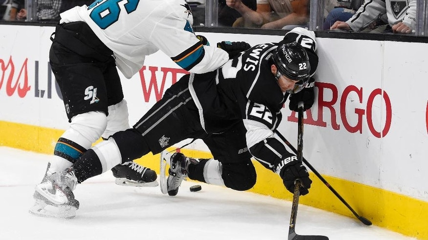 San Jose Sharks defenseman Roman Polak, left, of the Czech Republic, and Los Angeles Kings center Trevor Lewis vie for the puck during the second period of Game 2 in an NHL hockey Stanley Cup playoffs first-round series, Saturday, April 16, 2016, in Los Angeles. (AP Photo/Mark J. Terrill)