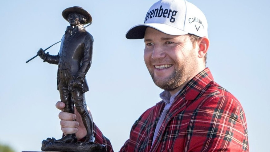 Branden Grace, of South Africa, holds the RBC Championship trophy after winning the final round of the RBC Heritage golf tournament in Hilton Head Island, S.C., Sunday, April 17, 2016. (AP Photo/Stephen B. Morton)
