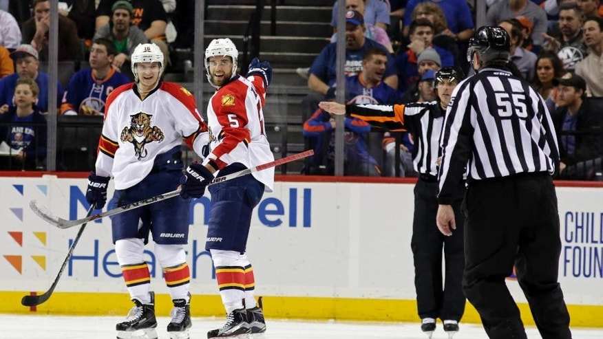 Florida Panthers defenseman Aaron Ekblad (5) looks back at linesman Shane Heyer (55) after scoring a goal during the second period in Game 3 of an NHL hockey first-round Stanley Cup playoff series against the New York Islanders, Sunday, April 17, 2016, in New York. After review, the goal was called off for an offside call. (AP Photo/Adam Hunger)