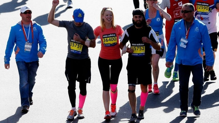 cross the finish line of the 118th Boston Marathon on April 21, 2014 in Boston, Massachusetts.