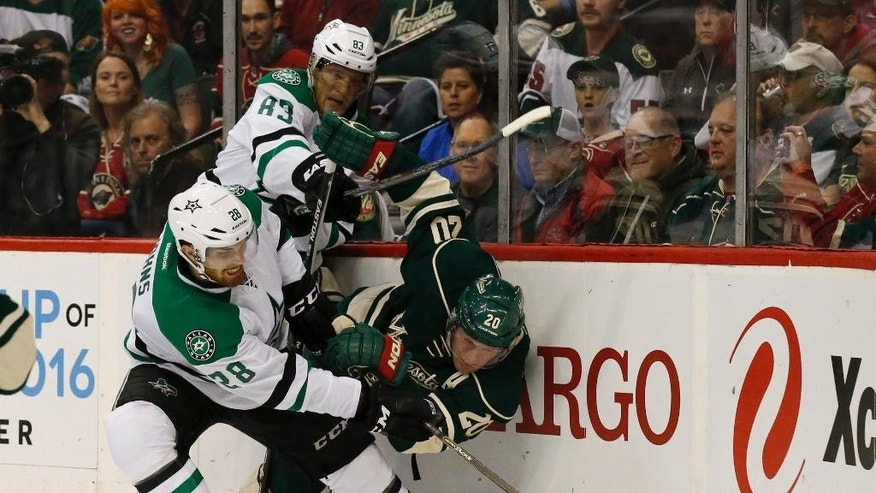 Minnesota Wild defenseman Ryan Suter (20) battles Dallas Stars defenseman Stephen Johns (28) and Stars right wing Ales Hemsky (83) during the first period of Game 3 in the first round of the NHL Stanley Cup playoffs in St. Paul, Minn., Monday, April 18, 2016. (AP Photo/Ann Heisenfelt)