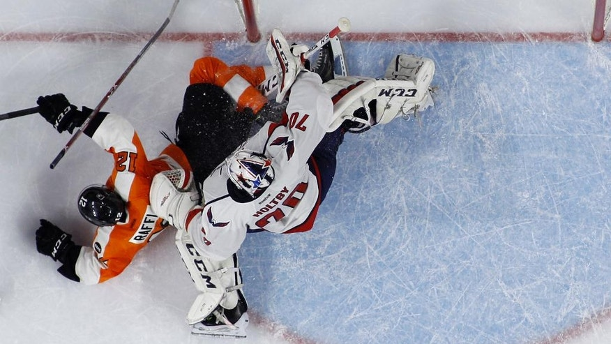 Philadelphia Flyers' Michael Raffl, left, collides with Washington Capitals' Braden Holtby during the second period of Game 3 in the first round of the NHL Stanley Cup hockey playoffs, Monday, April 18, 2016, in Philadelphia. (AP Photo/Matt Slocum)