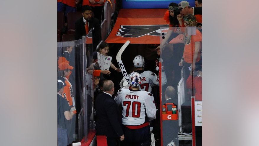 Washington Capitals' Braden Holtby gives his stick to a young girl as he walks off the ice after Game 3 in the first round of the NHL Stanley Cup hockey playoffs against the Philadelphia Flyers, Monday, April 18, 2016, in Philadelphia. Washington won 6-1. (AP Photo/Matt Slocum)