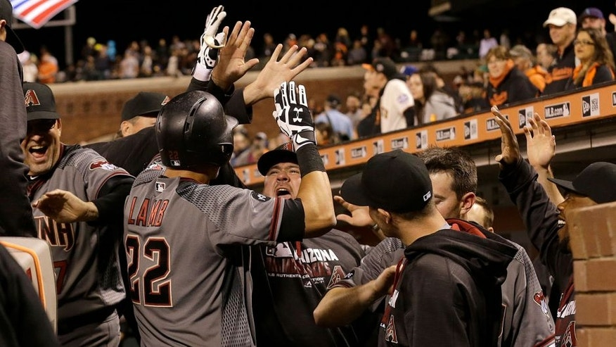 Arizona Diamondbacks' Jake Lamb (22) celebrates with teammates after hitting a solo home run against the San Francisco Giants during the ninth inning of a baseball game in San Francisco, Monday, April 18, 2016. (AP Photo/Jeff Chiu)
