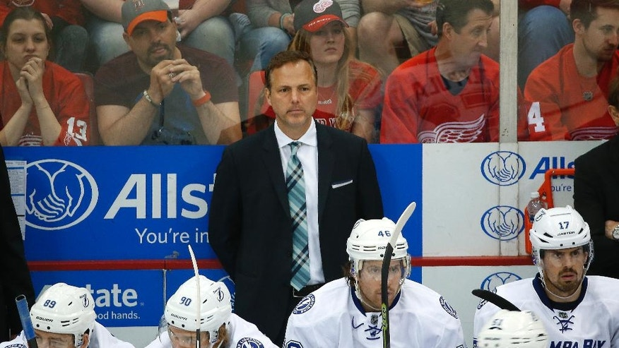 In this Sunday, April 17, 2016 photo, Tampa Bay Lightning head coach Jon Cooper watches against the Detroit Red Wings in the third period of Game 3 in a first-round NHL hockey Stanley Cup playoff series in Detroit. Cooper left Wall Street to be a lawyer, planning to eventually become a sports agent. To make ends meet as an attorney, he made $1,500 a month to handle cases for financially strapped clients in the middle of Michigan. Cooper's charm and communication skills helped him cut deals for defendants while quickly processing a lot of people in and out of the state district court. (AP Photo/Paul Sancya)