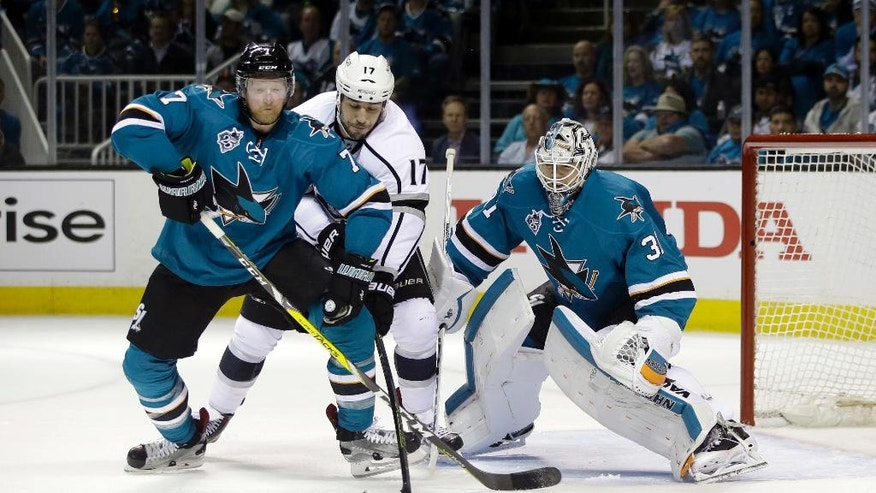 Los Angeles Kings' Milan Lucic, center, works next to the goal against San Jose Sharks' Paul Martin (7) and goalie Martin Jones during the second period of Game 3 of an NHL hockey first-round Stanley Cup playoff series Monday, April 18, 2016, in San Jose, Calif. (AP Photo/Marcio Jose Sanchez)