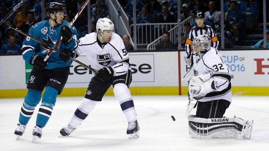 Los Angeles Kings goalie Jonathan Quick (32) stops a shot next to teammate Luke Schenn (52) and San Jose Sharks' Tomas Hertl, left, during the first period of Game 3 of an NHL hockey first-round Stanley Cup playoff series Monday, April 18, 2016, in San Jose, Calif. (AP Photo/Marcio Jose Sanchez)