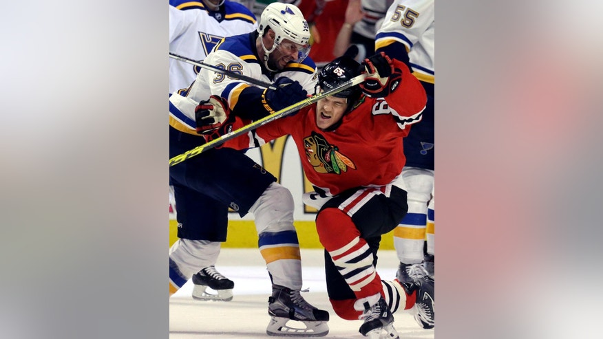 Chicago Blackhawks right wing Andrew Shaw, right, is hit by St. Louis Blues right wing Troy Brouwer during the second period in Game 4 of an NHL hockey first-round Stanley Cup playoff series Tuesday.
