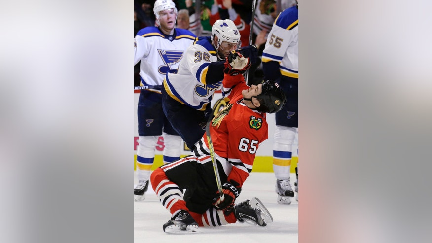 Chicago Blackhawks center Andrew Shaw (65) gets knocked down by St. Louis Blues right wing Troy Brouwer (36).