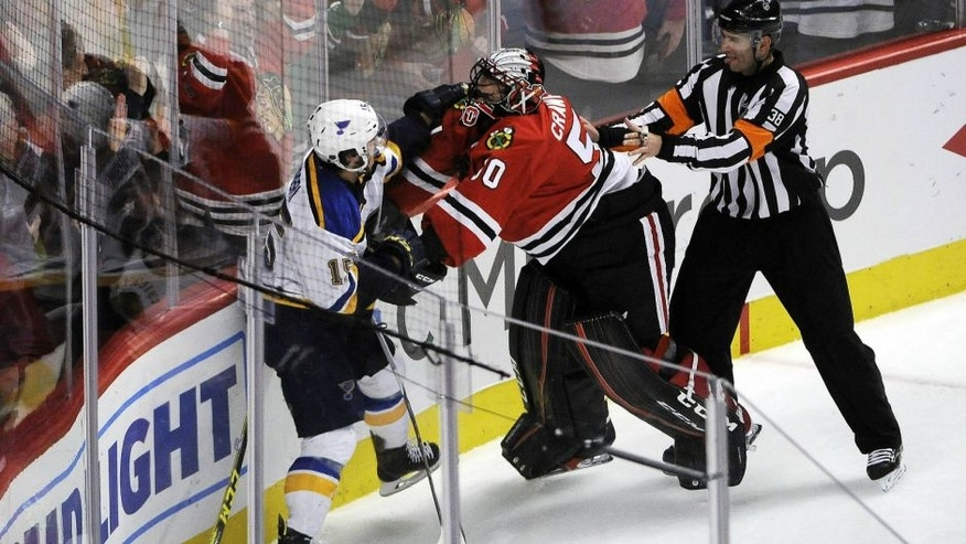Apr 19, 2016; Chicago, IL, USA; St. Louis Blues center Robby Fabbri (15) and Chicago Blackhawks goalie Corey Crawford (50) fight during the second period in game four of the first round of the 2016 Stanley Cup Playoffs at United Center. Mandatory Credit: David Banks-USA TODAY Sports