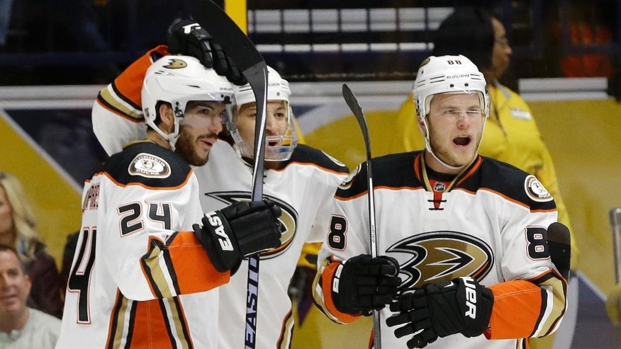 Anaheim Ducks left wing Jamie McGinn (88) celebrates with Simon Despres (24) and Chris Stewart, center, after scoring a goal against the Nashville Predators in the first period of Game 3 in an NHL hockey first-round Stanley Cup playoff series Tuesday, April 19, 2016, in Nashville, Tenn. (AP Photo/Mark Humphrey)