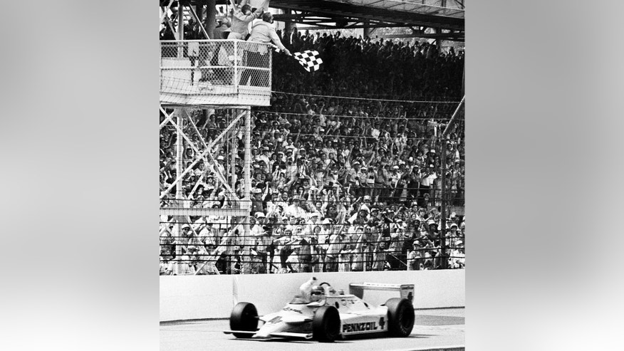 FILE - In this May 25, 1980 file photo, Johnny Rutherford gestures as he takes the checkered flag to win the 64th running of the Indianapolis 500 auto race at Indianapolis Motor Speedway in Indianapolis, Ind.  (AP Photo/File)