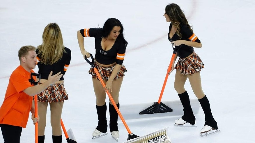 Ice crew personnel clean up promotional bracelets that were thrown onto the ice during the third period of Game 3 between the Philadelphia Flyers and the Washington Capitals in the first round of the NHL Stanley Cup hockey playoffs, Monday, April 18, 2016, in Philadelphia. Washington won 6-1. (AP Photo/Matt Slocum)