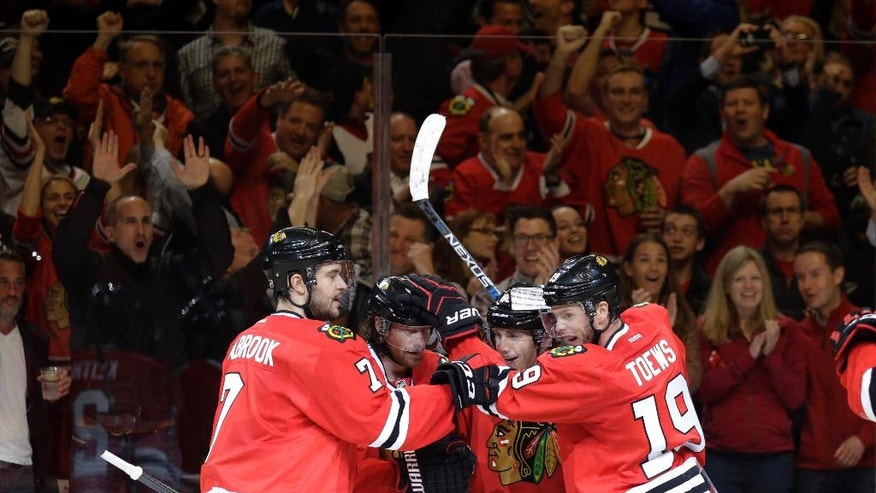 Chicago Blackhawks defenseman Duncan Keith, second from left, is congratulated by his teammates after scoring a goal during the second period in Game 4 of an NHL hockey first-round Stanley Cup playoff series against the St. Louis Blues, Tuesday, April 19, 2016, in Chicago. (AP Photo/Nam Y. Huh)